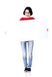 Mujer chocada que lleva a cabo al tablero en blanco Foto de archivo libre de regalías