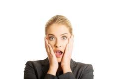 Mujer chocada que lleva a cabo las manos en la barbilla Fotos de archivo libres de regalías