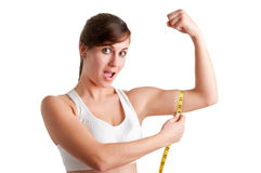 Mujer chocada que mide su bíceps Fotografía de archivo