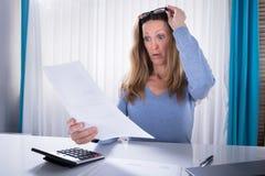 Mujer chocada que mira el documento en oficina fotos de archivo