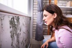 Mujer chocada que mira el molde en la pared foto de archivo libre de regalías