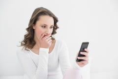 Mujer chocada que mira el teléfono móvil Fotografía de archivo