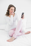 Mujer chocada que mira el teléfono móvil en cama Foto de archivo