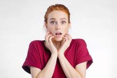 Mujer chocada que mira la cámara con la boca abierta y la cabeza conmovedora Imagen de archivo libre de regalías