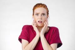 Mujer chocada que mira la cámara con la boca abierta y la cabeza conmovedora Fotos de archivo