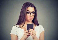 Mujer chocada que mira su teléfono móvil que ve malas noticias o las fotos fotografía de archivo