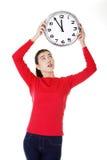 Mujer chocada que sostiene el reloj de la oficina Imagenes de archivo