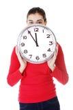 Mujer chocada que sostiene el reloj de la oficina Fotografía de archivo libre de regalías
