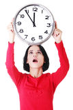 Mujer chocada que sostiene el reloj de la oficina Imagen de archivo libre de regalías