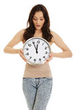Mujer chocada que sostiene el reloj grande Imagen de archivo libre de regalías