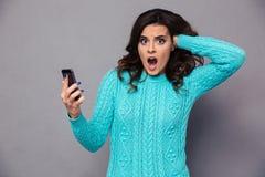 Mujer chocada que sostiene smartphone Foto de archivo
