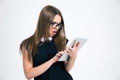 Mujer chocada que usa la tableta Foto de archivo