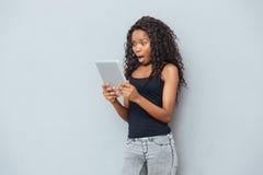 Mujer chocada que usa la tableta Imagen de archivo