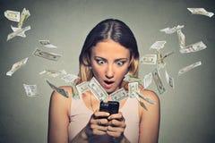 Mujer chocada que usa los billetes de dólar del smartphone que vuelan lejos de la pantalla fotografía de archivo libre de regalías
