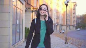 Mujer ciega con la mochila y los vidrios con un bastón que camina abajo de la calle y que habla en el teléfono metrajes
