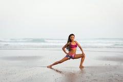 Mujer colorida que estira en la playa Foto de archivo libre de regalías