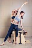 Mujer combinada de la silla de los pilates del wunda con el instructor Foto de archivo libre de regalías