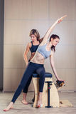 Mujer combinada de la silla de los pilates del wunda con el instructor Fotos de archivo