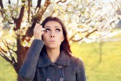 Mujer con alergias de la primavera usando descensos de ojo imágenes de archivo libres de regalías