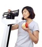Mujer con Apple en la escala preocupante de peso Foto de archivo libre de regalías