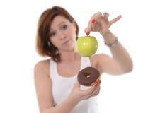 Mujer con Apple y el buñuelo del chocolate en manos Foto de archivo libre de regalías