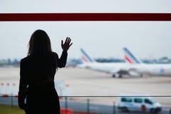 Mujer con bulto de mano en el aeropuerto internacional, mirando a través de la ventana los aviones foto de archivo libre de regalías