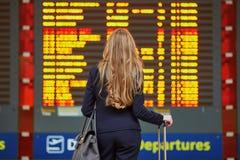 Mujer con bulto de mano en el terminal de aeropuerto internacional, mirando al tablero de la información imagenes de archivo