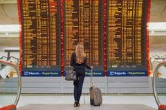 Mujer con bulto de mano en el terminal de aeropuerto internacional, mirando al tablero de la información Imagen de archivo