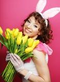 Mujer con Bunny Ears que sostiene tulipanes amarillos Imagenes de archivo