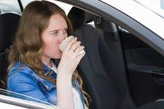 Mujer con café en el coche Fotografía de archivo libre de regalías