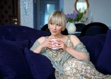 Mujer con café en el sofá Foto de archivo libre de regalías