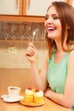 Mujer con café que come la torta poner crema glotonería Fotos de archivo