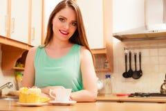 Mujer con café y la torta en cocina glotonería imagen de archivo