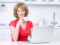 Mujer con café de consumición de la computadora portátil Imágenes de archivo libres de regalías