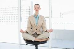 Mujer con clase atractiva que se sienta en la posición de loto respecto a su silla de eslabón giratorio Foto de archivo