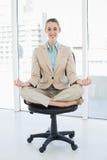 Mujer con clase hermosa que se sienta en la posición de loto respecto a su silla de eslabón giratorio Imagenes de archivo