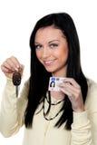 Mujer con claves del coche y la licencia de programas pilotos. Conducción Foto de archivo libre de regalías