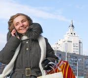 Mujer con compras y un teléfono en la ciudad Foto de archivo