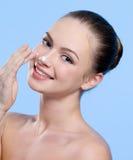Mujer con crema en su nariz Fotos de archivo