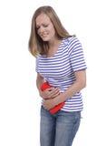 Mujer con dolor caliente de la botella y de estómago Fotografía de archivo libre de regalías