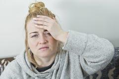 Mujer con dolor de cabeza Mujer del ama de casa en un sofá con el dolor de cabeza imagen de archivo