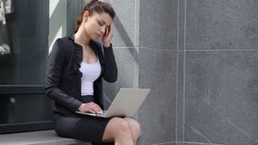 Mujer con dolor de cabeza usando el ordenador portátil fuera de la oficina almacen de video
