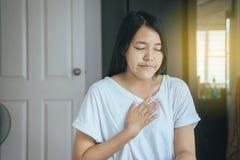Mujer con dolor de pecho fuerte y manos que tocan su pecho, síntoma del ataque del corazón Imágenes de archivo libres de regalías