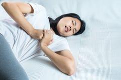 Mujer con dolor de pecho fuerte y manos que tocan su pecho, síntoma del ataque del corazón Foto de archivo