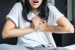 Mujer con dolor de pecho fuerte y manos que tocan su pecho, síntoma del ataque del corazón Imagen de archivo