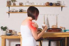 Mujer con dolor en el hombro que sufre en casa foto de archivo