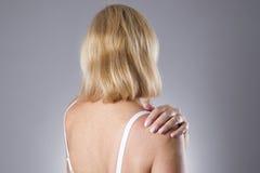 Mujer con dolor en hombro Dolor en el cuerpo humano Imagen de archivo libre de regalías