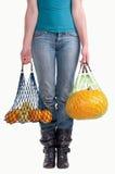 Mujer con dos bolsos de tienda de comestibles amarillos de la fruta Imágenes de archivo libres de regalías