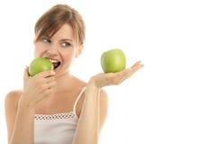 Mujer con dos manzanas verdes Fotos de archivo