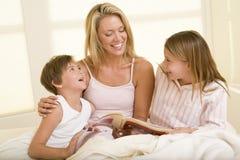 Mujer con dos niños jovenes que se sientan en cama Fotografía de archivo